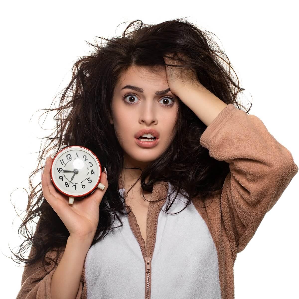 寝坊した若い女性が時間の過ぎた時計を持っている様子