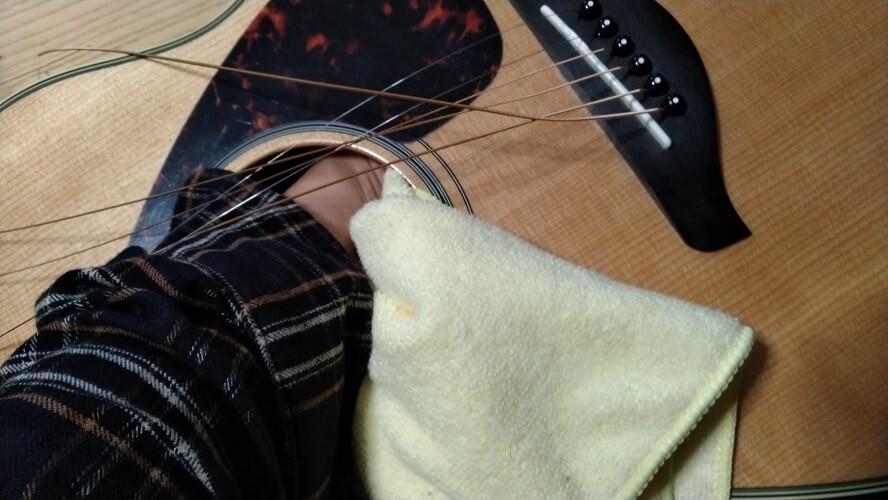 ギターホールに手を入れて中からブリッジピンを押し出している画像