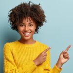 黄色い服を着た女性が指でポイントを指している様子。