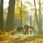 緑の多い公園で筋トレをする強い女性。