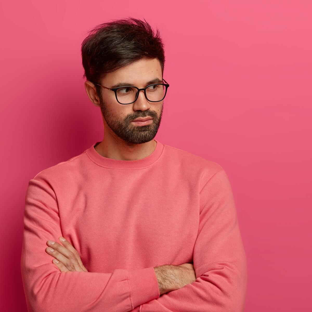 眼鏡をかけた男性が腕組みをしている様子。
