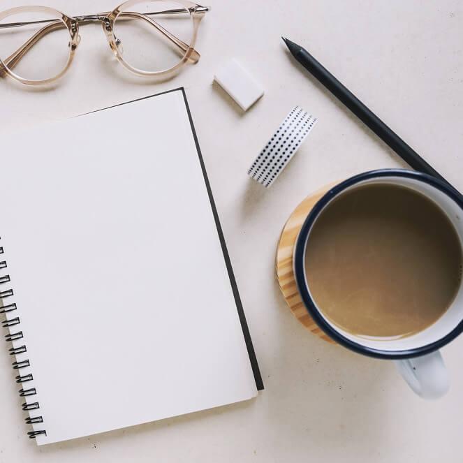 机の上に手帳とコーヒーが置いてある様子