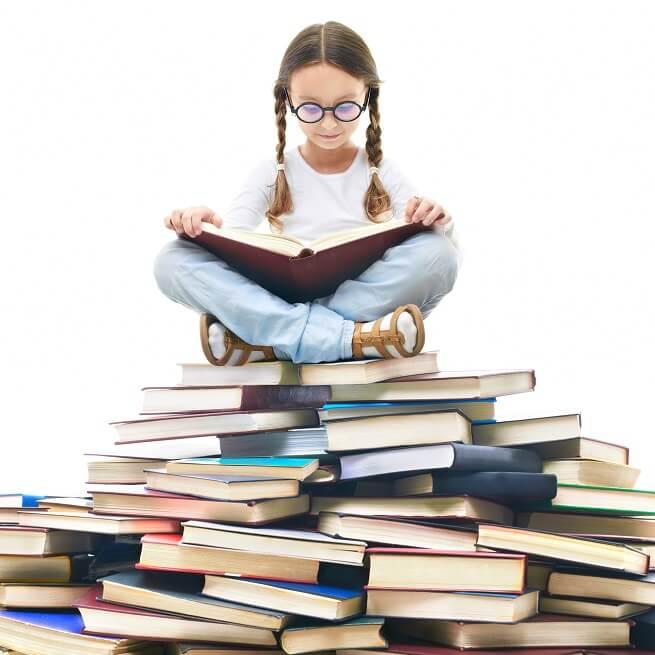 たくさんの本の上に座る少女