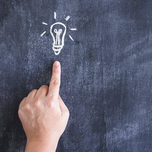 黒板に電球の絵をチョークで描き、人差し指で刺した写真で、閃きを表している