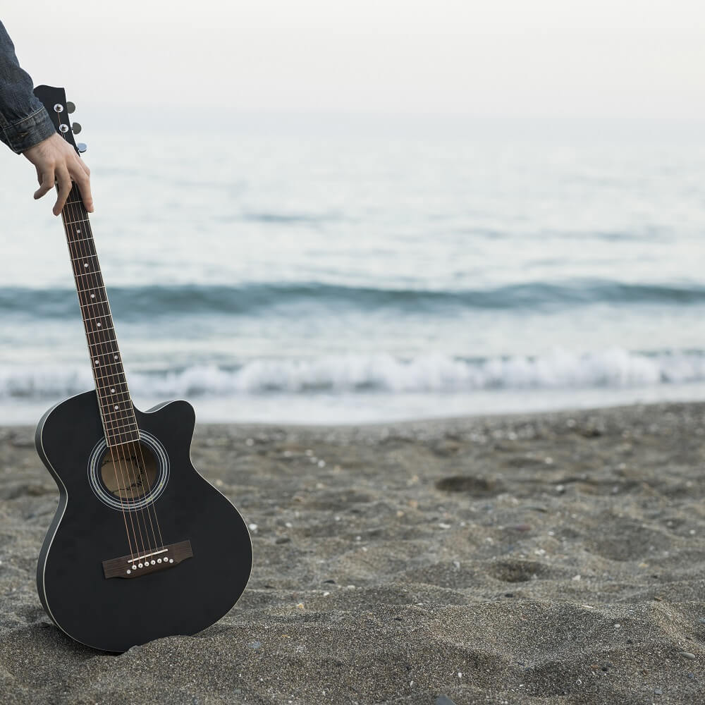 海辺でアコギを使って作曲の特訓をしている風景