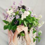 結婚式で顔を花束で隠している様子の花嫁。