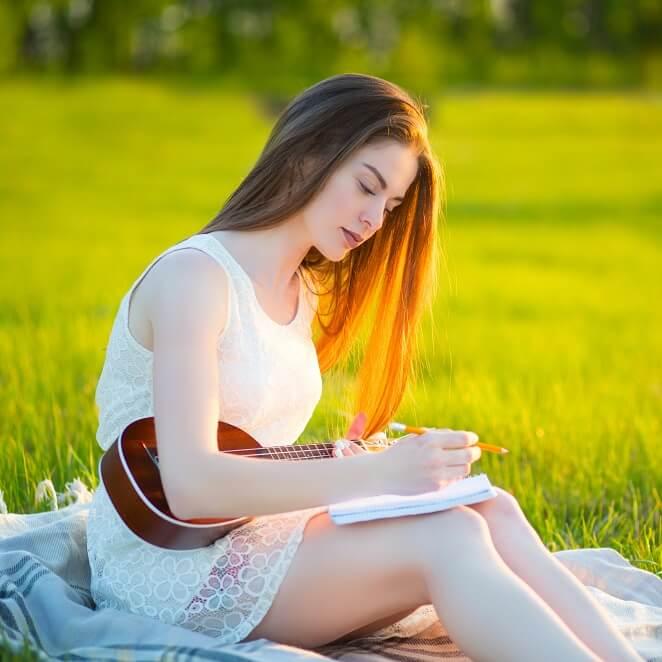女の子が草原で歌詞を考えている様子