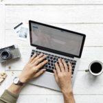 白い机の上にあるノートパソコンにタイピングしている様子。