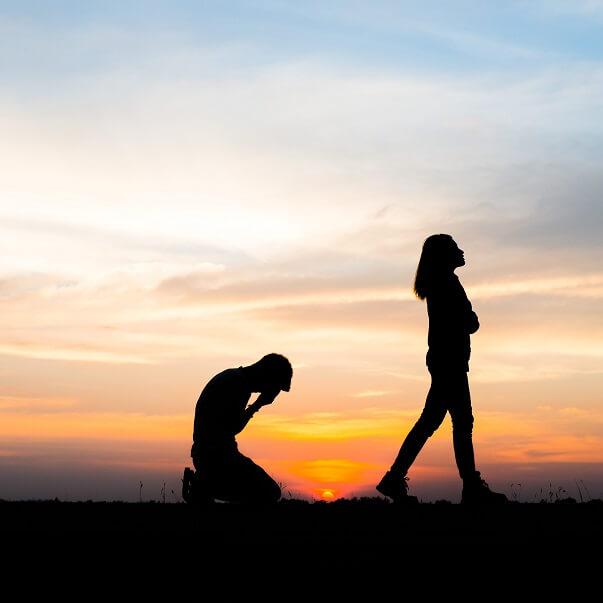 パートナーの女性に振られた男性の様子。夕焼けの背景に逆行の女性と男性。