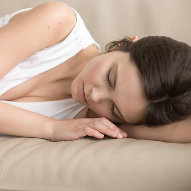 ソファの上で二度寝をしてしまう女性。