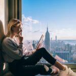 高層階からニューヨークを望む窓の前でほほ笑むノマド女性