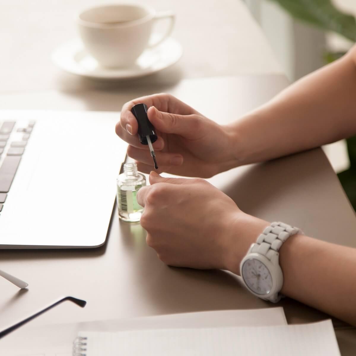 オフィスでネイルをする女性。