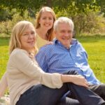 両親と芝生の上でくつろぐ女性。