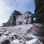 崖に挑むブーツをはいた男性。