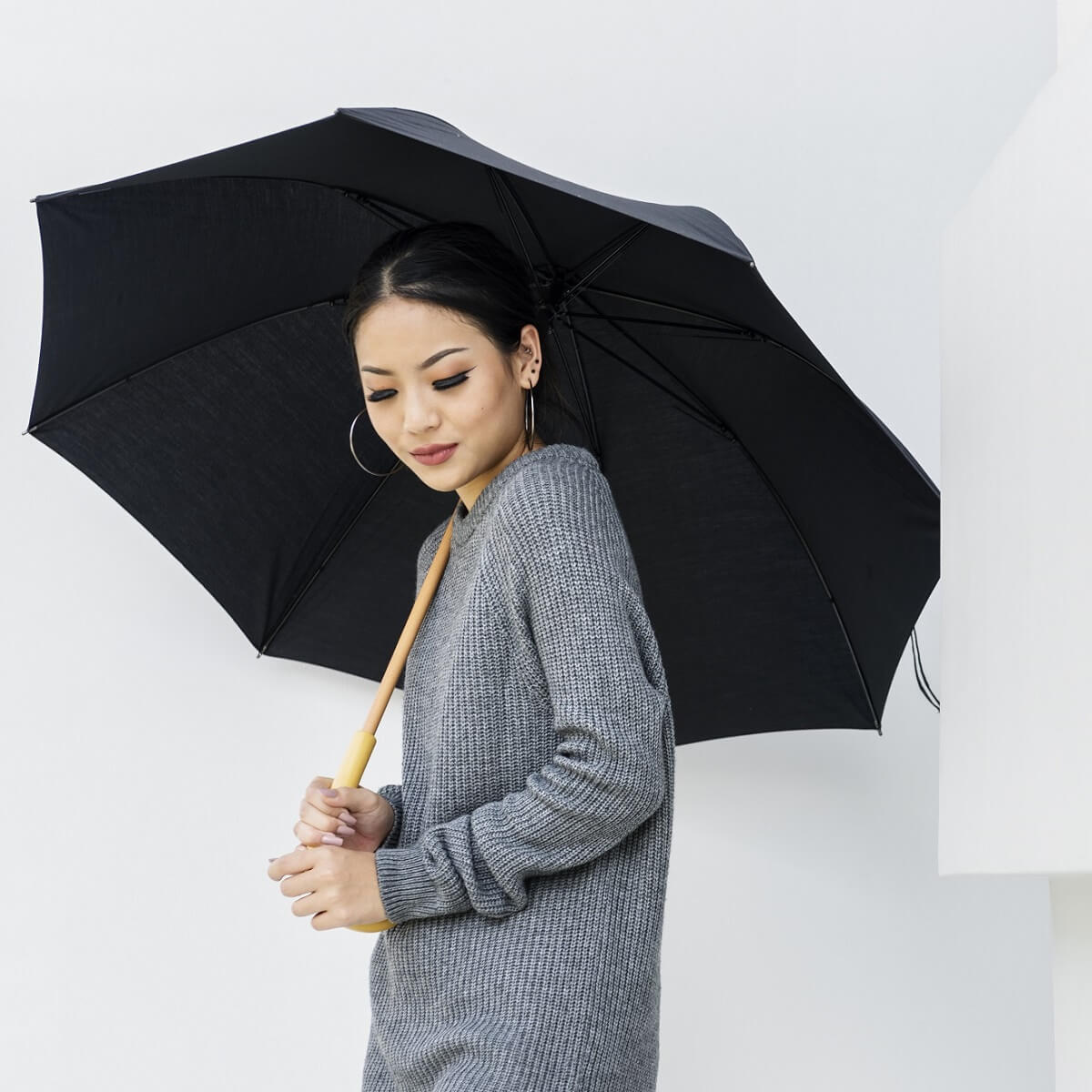黒の傘をさす女性。
