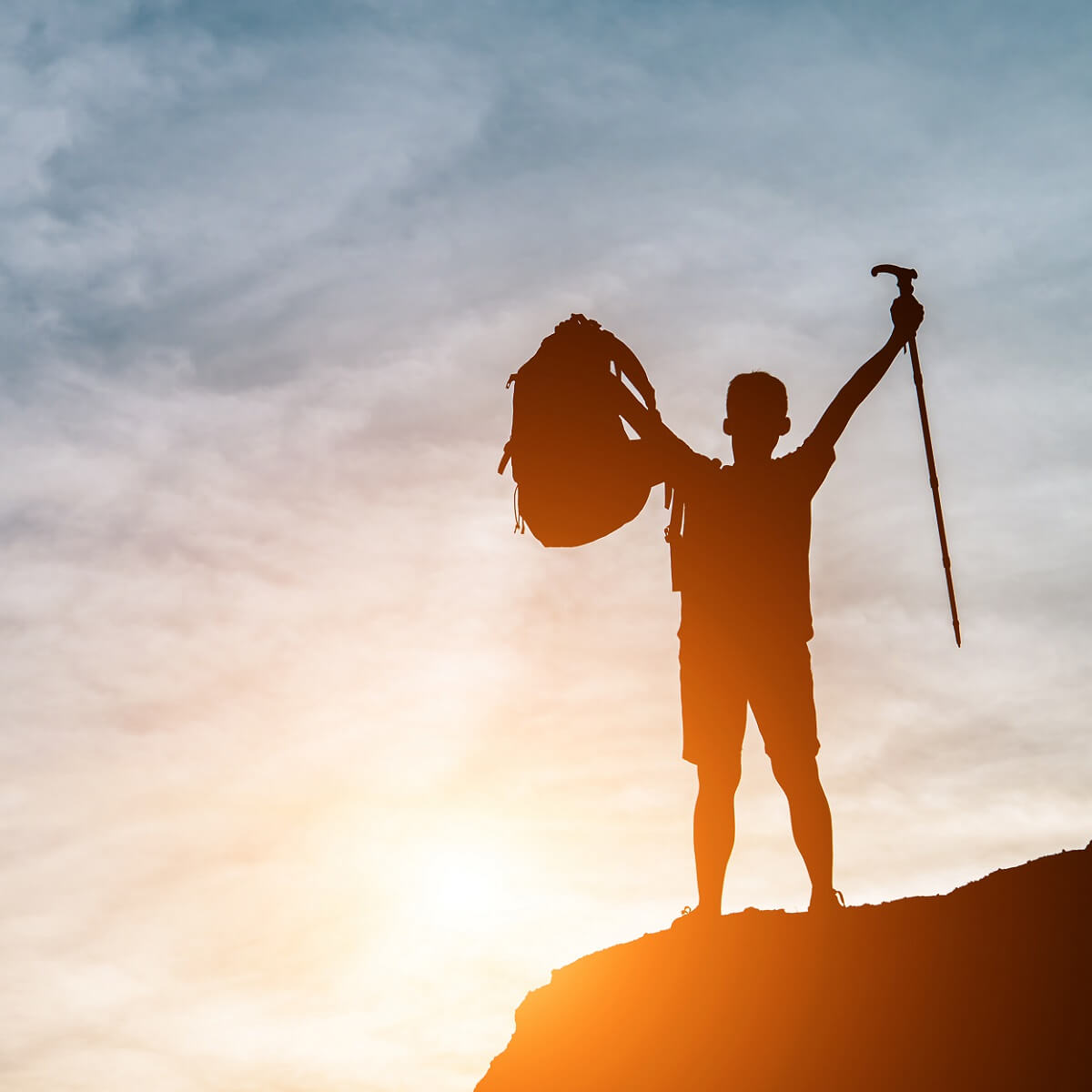 山の山頂に立つ男性の写真。