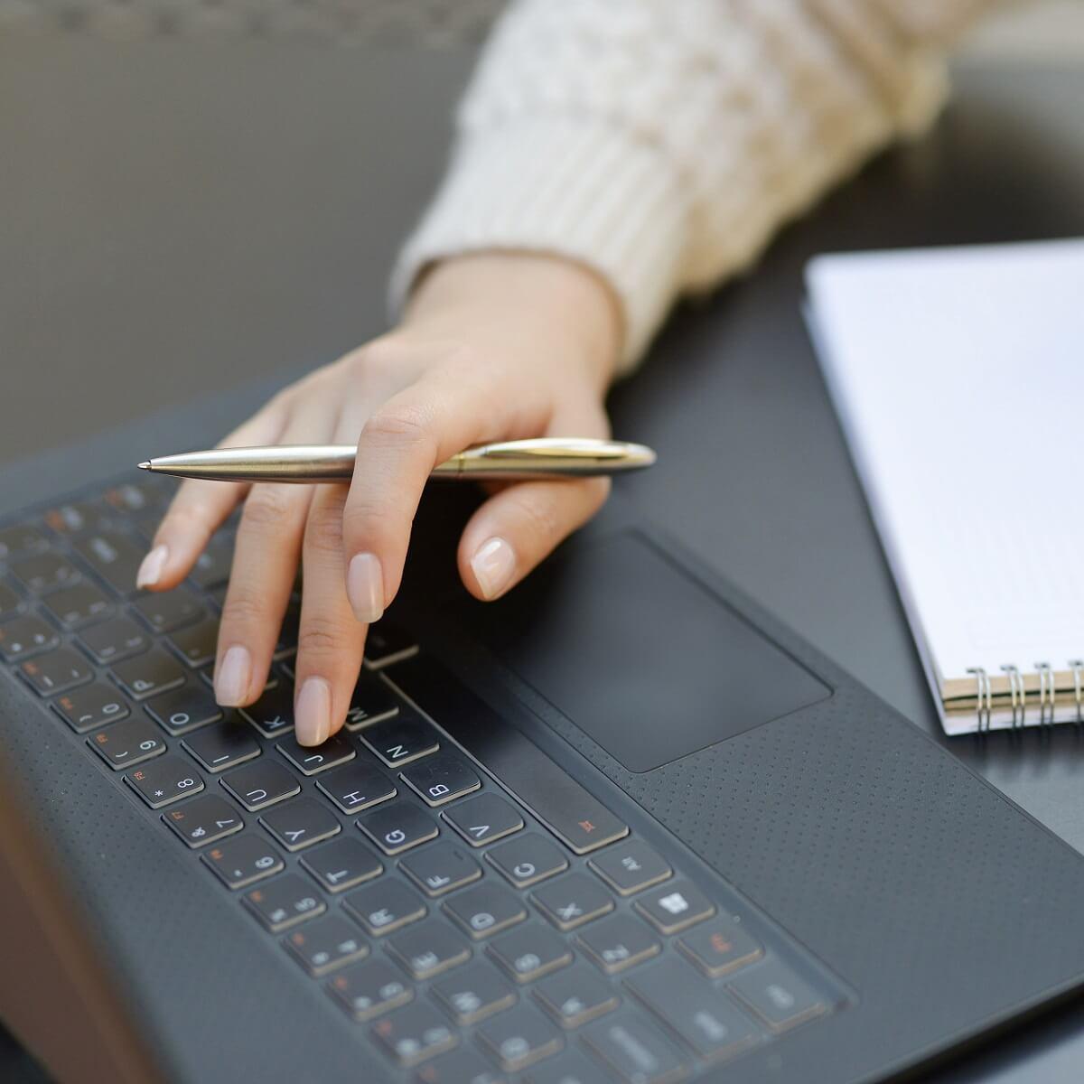 ノートパソコンとメモ帳の画像。