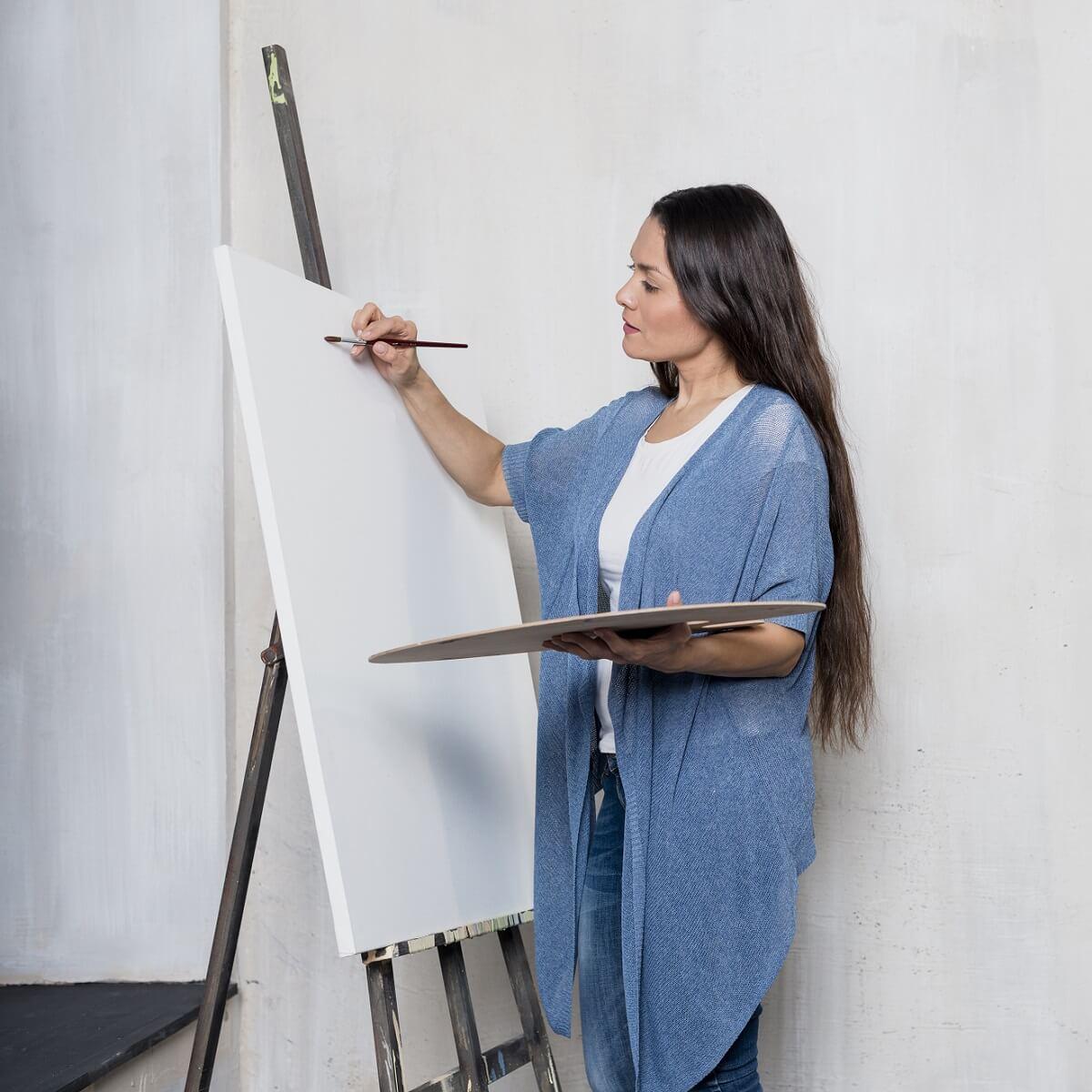 キャンバスに絵を描く女性。