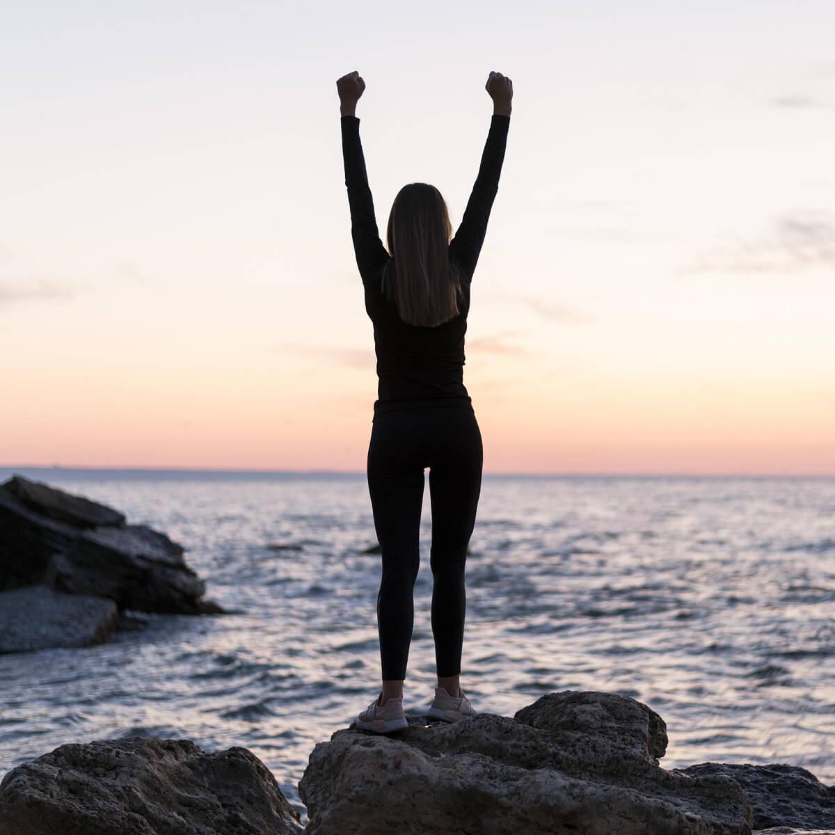 女性が夕方に海岸で伸びをしている様子。
