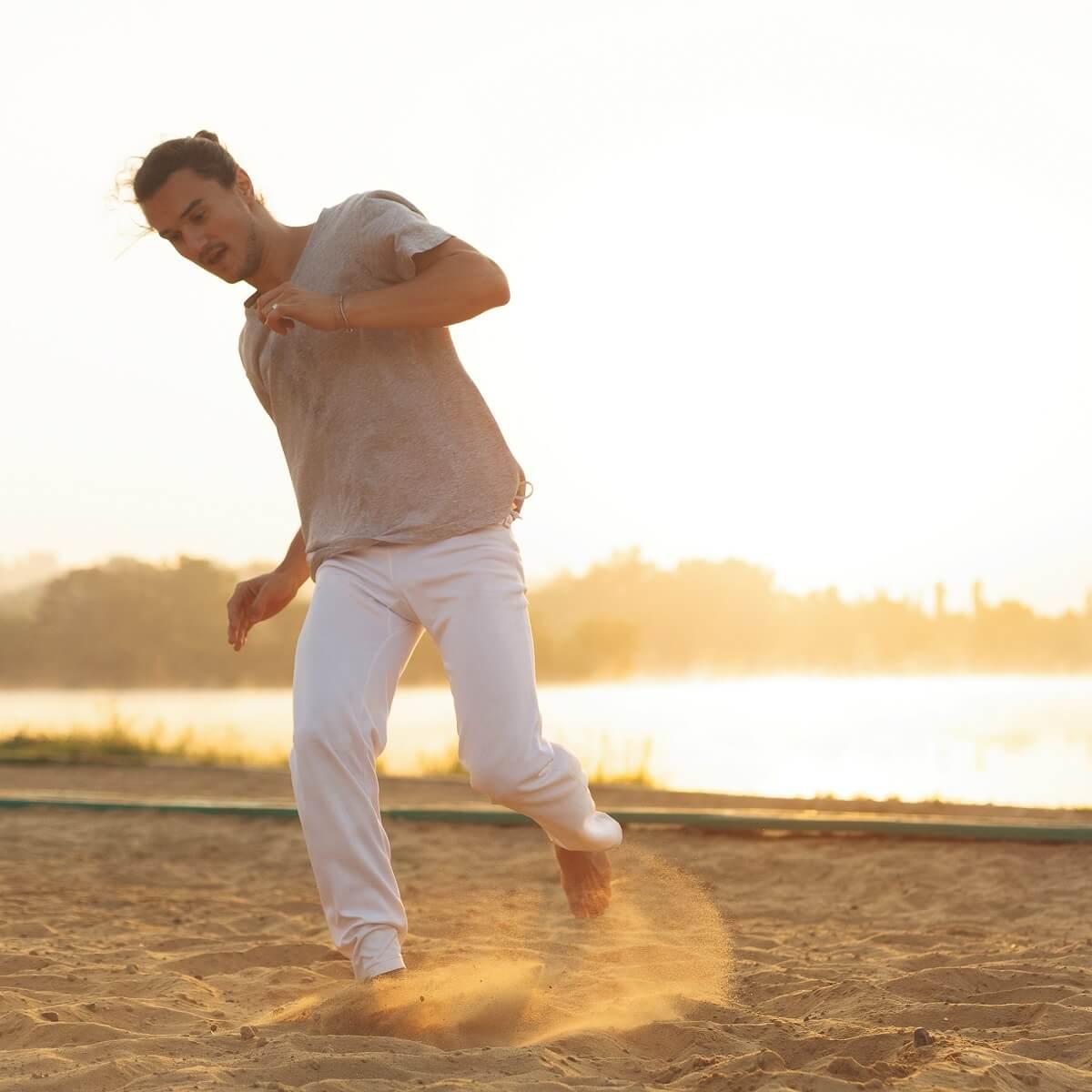 正装で砂浜でかけまわる男性。