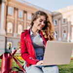 大学のキャンパスでノートパソコンを触っている女性の様子。