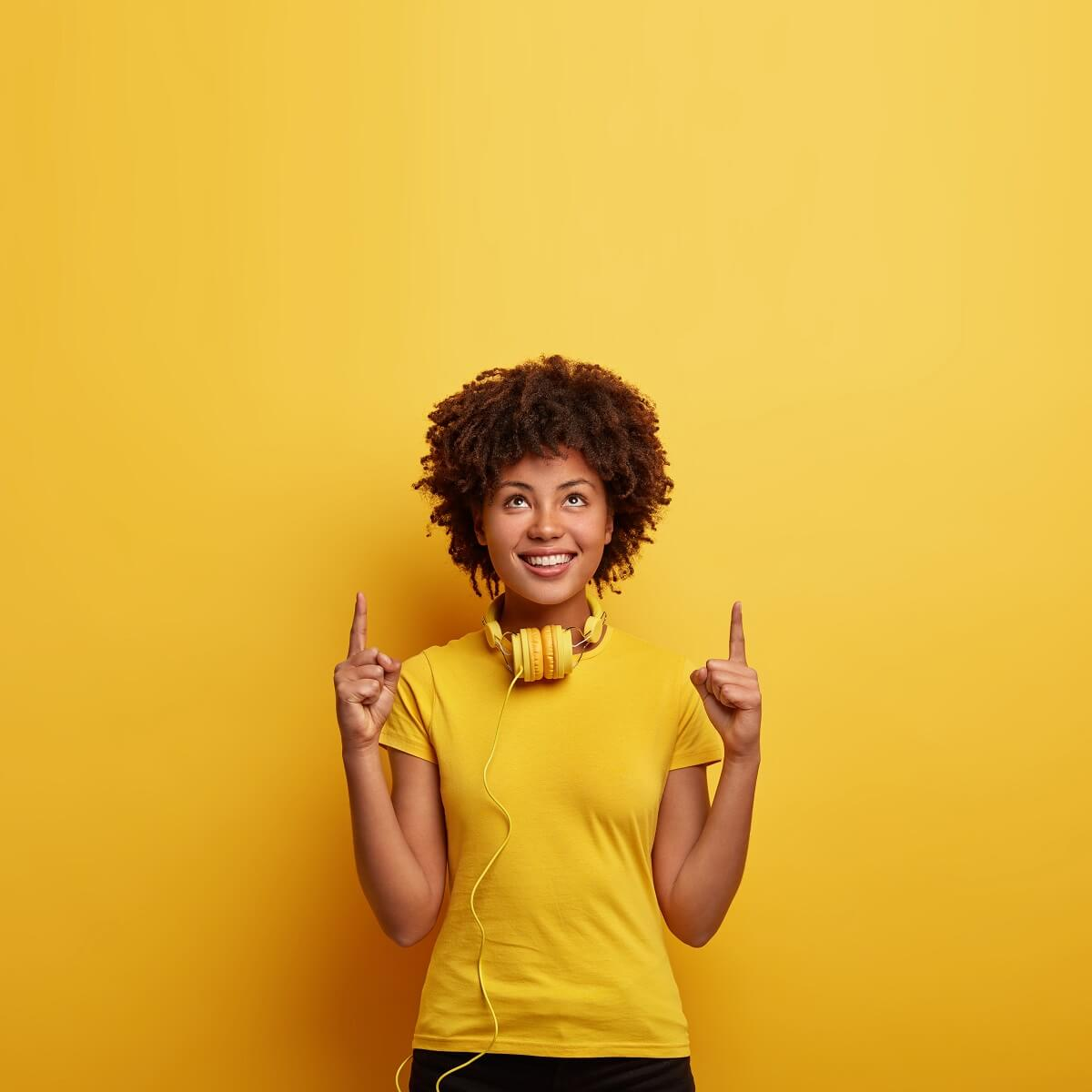 ヘッドホンを首にかけた外国人の女性が指を上に指している様子。