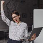 女性がノートパソコンを片手にガッツポーズをしている様子。