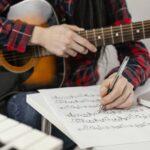 ギターを片手に作曲している様子。