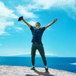 海の前で両手を上げて自由を感じている男性。