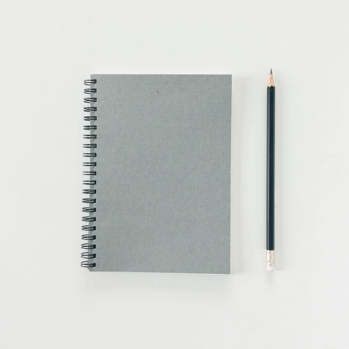 新品のグレーのノートと鉛筆。