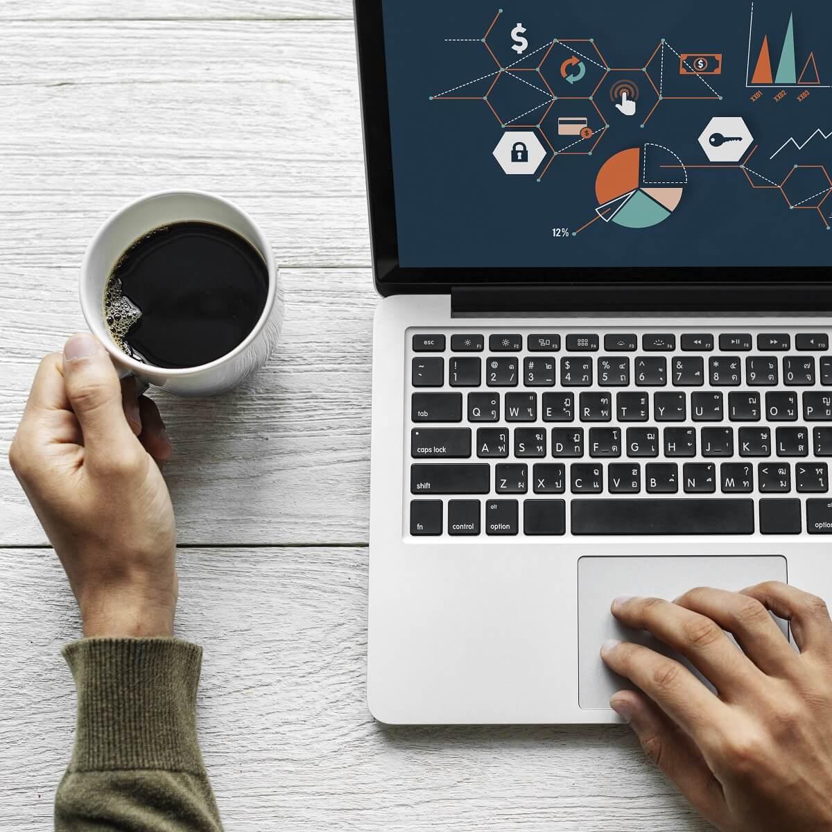 白のテーブルの上にノートパソコンとコーヒーが置かれている様子。