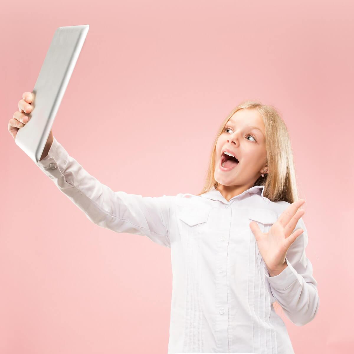 ノートパソコンを持っているうれしそうな少女。