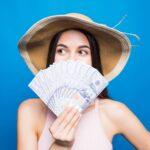 札束の扇を作って口元を覆っている女性。