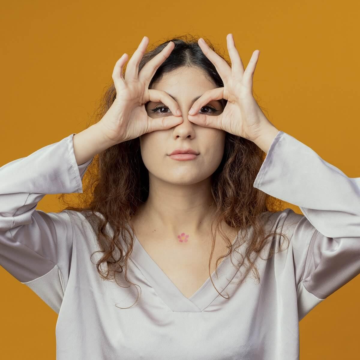 手で眼鏡マスクを作る女性。